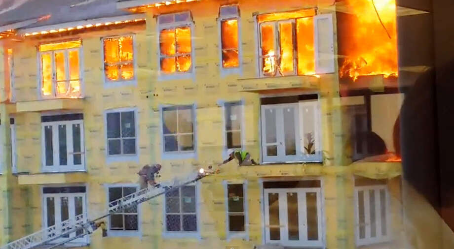 In this image taken from video provided by Karen Jones, a worker reaches for an extension ladder to escape a raging fire as firefighters battle a five-alarm blaze at a construction site Tuesday, March 25, 2014, in Houston. The cellphone video, shot by Karen Jones from her nearby office, shows the dramatic rescue of the worker from the burning apartment complex that was under construction. (AP Photo/Karen Jones) NO SALES Photo: Karen Jones, HONS / Karen Jones