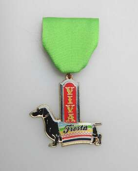 Joni Drought's Viva Fiesta medal pays tribute to the doxie, or dachshund, of which Drought has had several. She won't sell them but will be out at Fiesta events handing them out. Photo: Juanito M. Garza, San Antonio Express-News / San Antonio Express-News