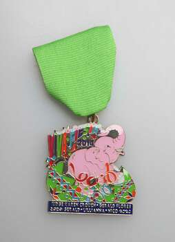 "Karen Crouch ""Lucky Pink"" Fiesta 2014 medal, which the former judge and her family design together and hand out for free during Fiesta. She also says you can have one, if you message her on Facebook.com/Karen.crouch8. Photo: Juanito M. Garza, San Antonio Express-News / San Antonio Express-News"