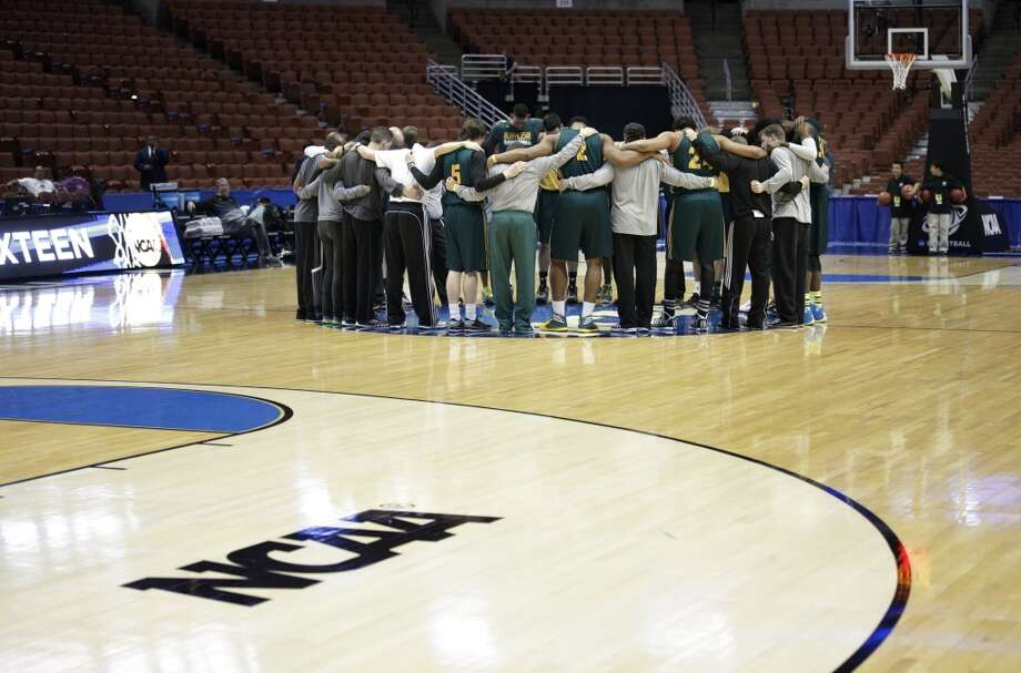 Baylor players gather around the NCAA logo during practice at the NCAA college basketball tournament on Wednesday, March 26, 2014, in Anaheim, Calif. Baylor plays Wisconsin in a regional semifinal on Thursday. Photo: Jae C. Hong, Associated Press
