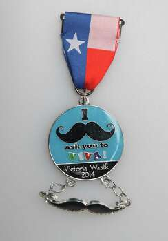 "Victoria Wasik's Fiesta medal, ""I Mustache Ask You to Viva!"" honors her last name, which translates loosely from Polish to ""wasy"" or ""mustache,"" the junior at Churchill High School says. She gives her medals away to friends. Photo: Juanito M. Garza, San Antonio Express-News / San Antonio Express-News"