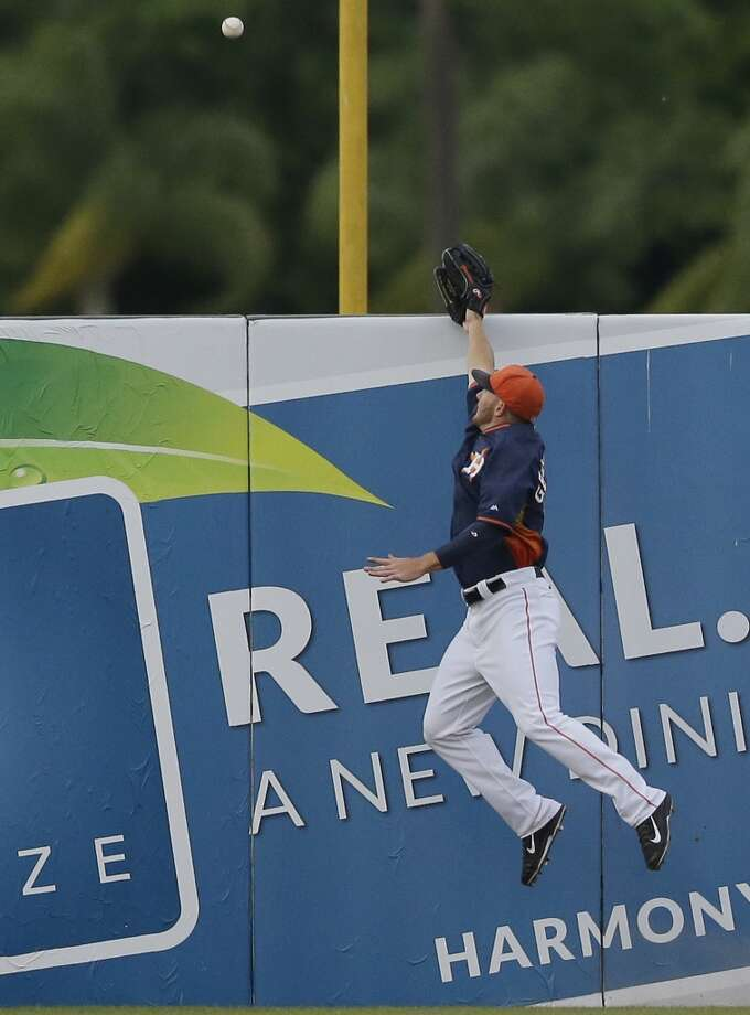 Astros left fielder Robbie Grossman jumps but can't reach the two-run home run by Anthony Recker. Photo: Carlos Osorio, Associated Press