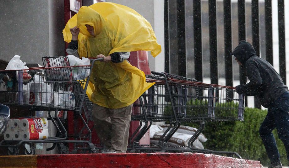 A shopper and a cart wrangler at the Brook Hollow H-E-B grocery store battle wet and windy elements Wednesday. Photo: Photos By John Davenport / San Antonio Express-News / ©San Antonio Express-News/Photo may be sold to the public