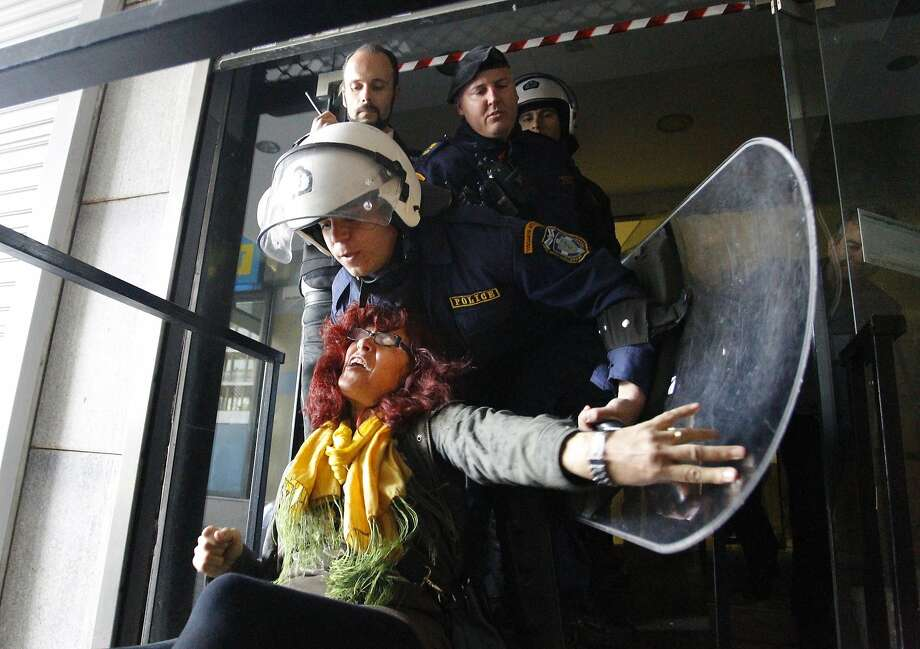 Riot police restrain a protesting cleaning staff worker at the side entrance of the Finance Ministry, in Athens, on Wednesday, March 26, 2014. Police forcibly expelled the protesters, who have lost their jobs in austerity staff cuts, from the ministry building after a request was denied for protest representatives to meet ministry officials. (AP Photo/Kostis Ntantamis) Photo: Kostis Ntantamis, Associated Press