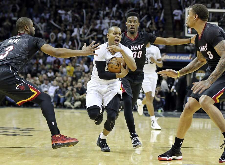 San Antonio Spurs' Patty Mills looks for room between Miami Heat's Dwyane Wade (left), Norris Cole, and Michael Beasley during second half action Thursday March 6, 2014 at the AT&T Center. The Spurs won 111-87. Photo: Edward A. Ornelas, San Antonio Express-News