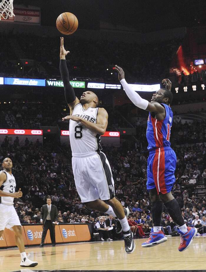 Patty Mills (8) of the San Antonio Spurs lays up the ball as Will Bynum of the Detroit Pistons defends during NBA action in the AT&T Center on Wednesday, Feb. 26, 2014. Photo: Billy Calzada, San Antonio Express-News