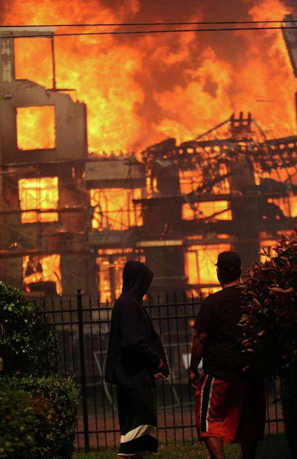 People view the fire which ignited inside an apartment building construction site at the corner of Marconi St. and Dallas Ave. on March 25, 2014, in Houston, Tx. Photo: Mayra Beltran, Houston Chronicle / © 2014 Houston Chronicle