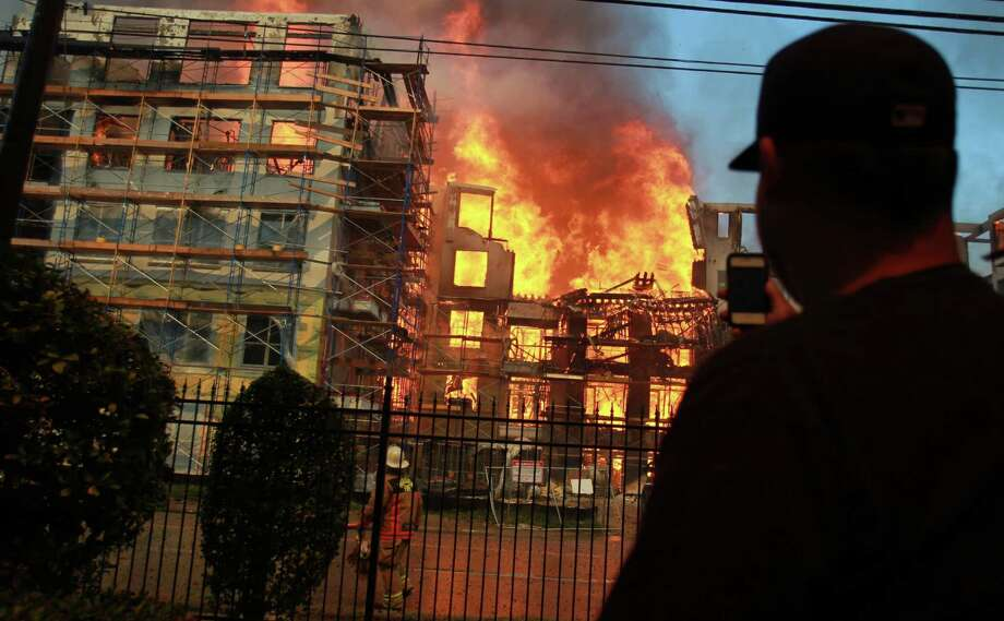A young man views a five-alarm fire that ignited inside an apartment construction site at the corner of Marconi St. and Dallas Ave. on March 25, 2014, in Houston, Tx. Photo: Mayra Beltran, Houston Chronicle / © 2014 Houston Chronicle