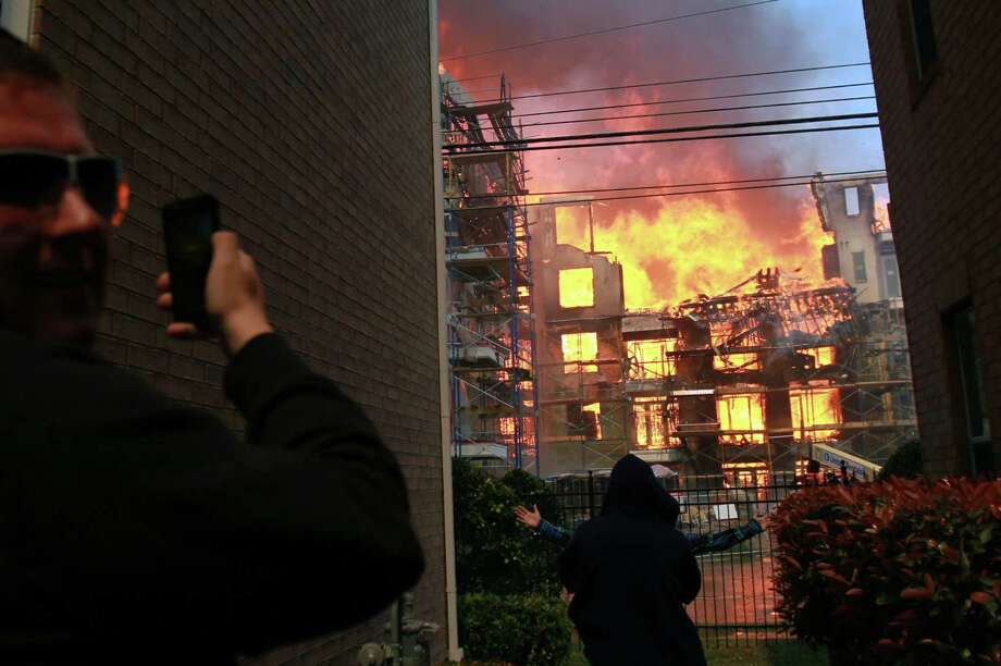 Spectators watch an apartment under construction burn as Houston firefighters work to extinguish a five-alarm fire at a construction site Tuesday, March 25, 2014, in Houston. Fire officials said more than 200 emergency personnel were at the scene Tuesday afternoon and were working to protect nearby buildings. (Houston Chronicle, Mayra Beltran)  Photo: Mayra Beltran, Houston Chronicle / Houston Chronicle