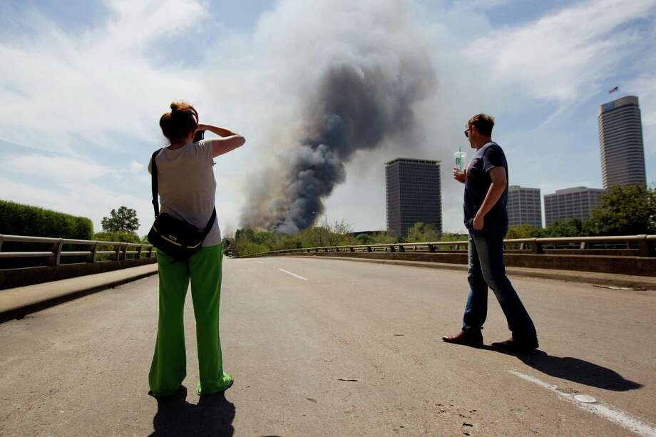 A couple stops to watch the plume of smoke on Studewood as firefighters battled a large 5-alarm blaze Tuesday afternoon at an apartment building under construction on West Dallas near Montrose Tuesday, March 25, 2014, in Houston. Flames engulfed the apartment complex as 200 firefighters in 80 units fought to gain an upper hand on the blaze. The five-story, 368-unit building was destroyed. No injuries were reported. Photo: Johnny Hanson, Houston Chronicle / © 2014  Houston Chronicle