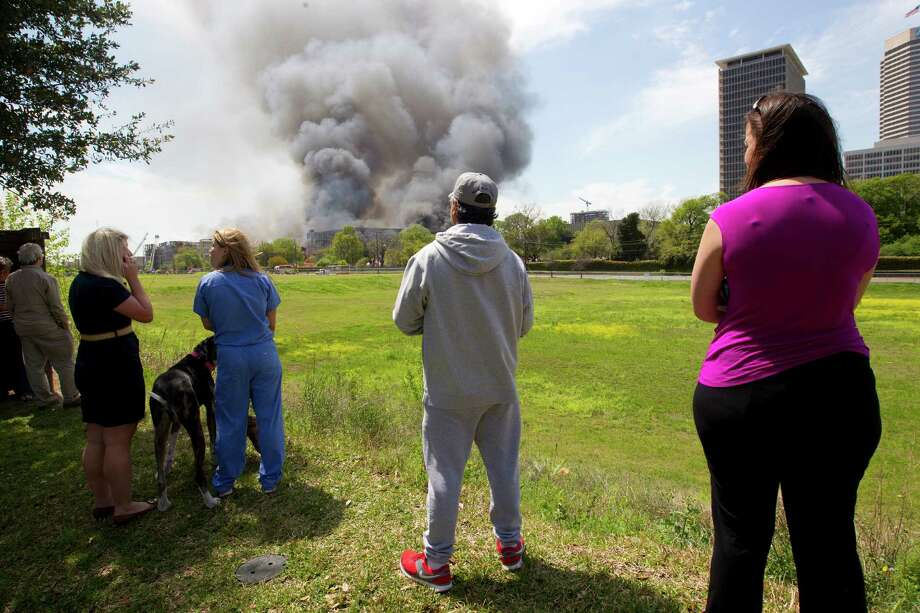 Onlookers watch as firefighters battled a large 5-alarm blaze Tuesday afternoon at an apartment building under construction on West Dallas near Montrose Tuesday, March 25, 2014, in Houston. Flames engulfed the apartment complex as 200 firefighters in 80 units fought to gain an upper hand on the blaze. The five-story, 368-unit building was destroyed. No injuries were reported. Photo: Johnny Hanson, Houston Chronicle / © 2014  Houston Chronicle