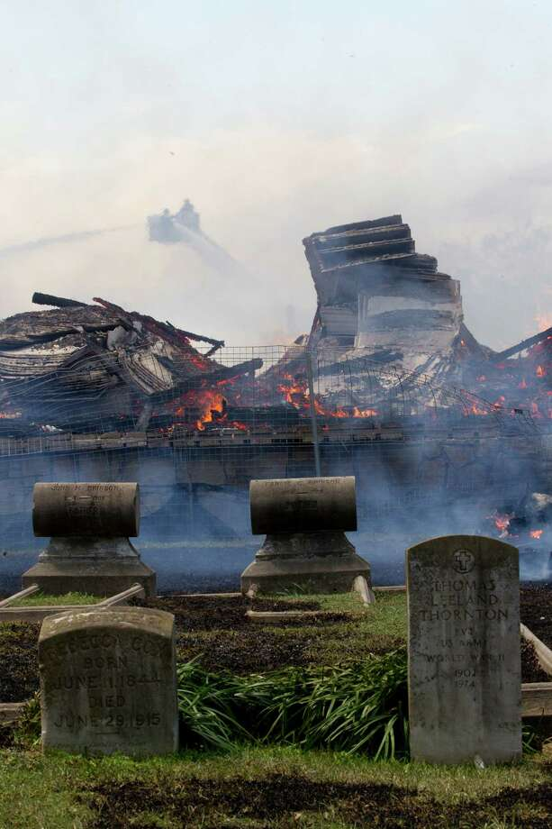 Gravestones in the Magnolia Cemetery of Houston get covered in smoke as firefighters battled a large 5-alarm blaze Tuesday afternoon at an apartment building under construction on West Dallas near Montrose Tuesday, March 25, 2014, in Houston. Flames engulfed the apartment complex as 200 firefighters in 80 units fought to gain an upper hand on the blaze. The five-story, 368-unit building was destroyed. No injuries were reported. Photo: Johnny Hanson, Houston Chronicle / © 2014  Houston Chronicle