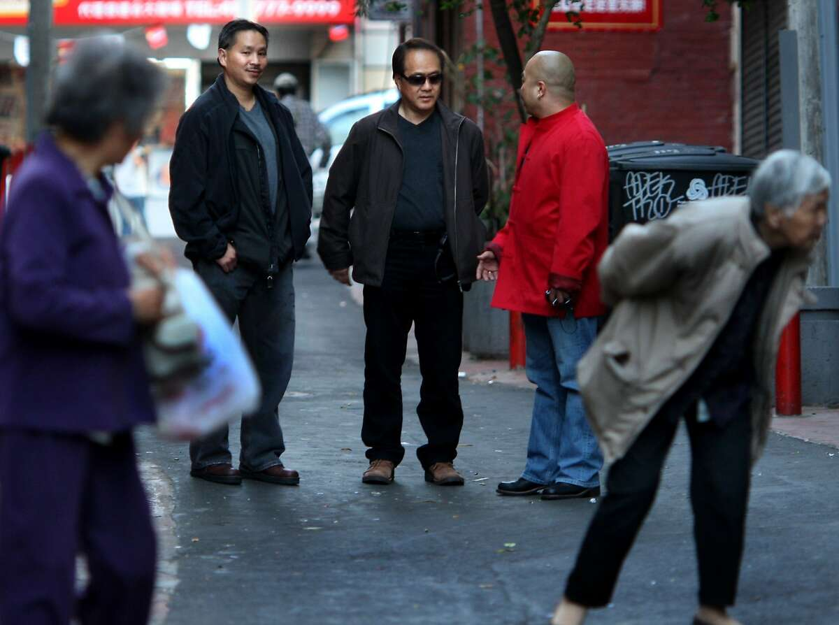 In Chinatown's Spofford Alley, SFPD inspectors Jameson Pon, left, and Henry Seto, center, stop to talk with Raymond Chow, the chairman of the Ghee Kung Tong nearby in 2007. SFPD Inspectors Henry Seto and Jameson Pon are members of the Gang Task Force. Their beat is San Francisco's Chinatown where they both grew up. Like others in the task force, they spend their evenings trying to find suspects and gather information in the maze of Asian culture that is Chinatown.