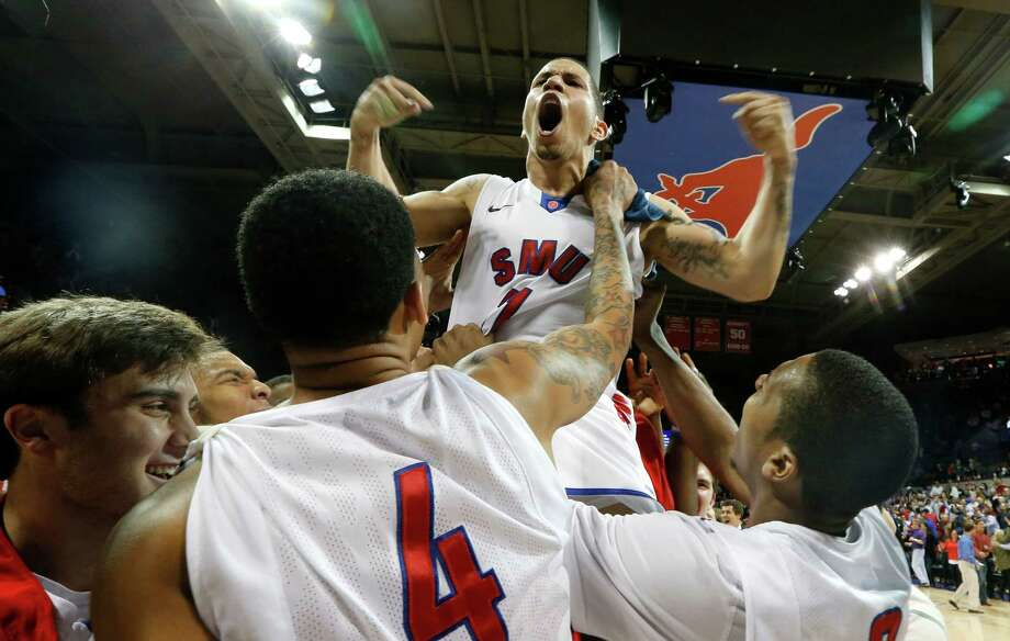 SMU guard Nic Moore (11) is lifted in the air and celebrates with fans after an NCAA college basketball game against California in the quarterfinals of the NIT Wednesday, March 26, 2014, in Dallas. SMU won 67-65. (AP Photo/Sharon Ellman) Photo: Sharon Ellman, Associated Press / FR170032 AP