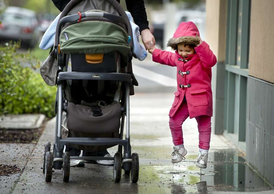The puddle destroyer of Davis: Two-year-old Isabelle Hatcher jumps in a puddle on a rainy day in downtown Davis, Calif. Her mother said she splashed every puddle they encountered on their walk. Photo: Randy Pench, McClatchy-Tribune News Service