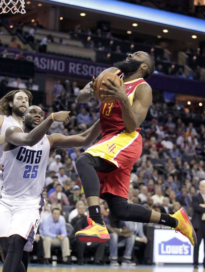 Houston Rockets' James Harden (13) tries to complete the play despite being fouled by Charlotte Bobcats' Al Jefferson (25) during the second half of an NBA basketball game in Charlotte, N.C., Monday, March 24, 2014. The Rockets won 100-89. (AP Photo/Bob Leverone) Photo: Associated Press