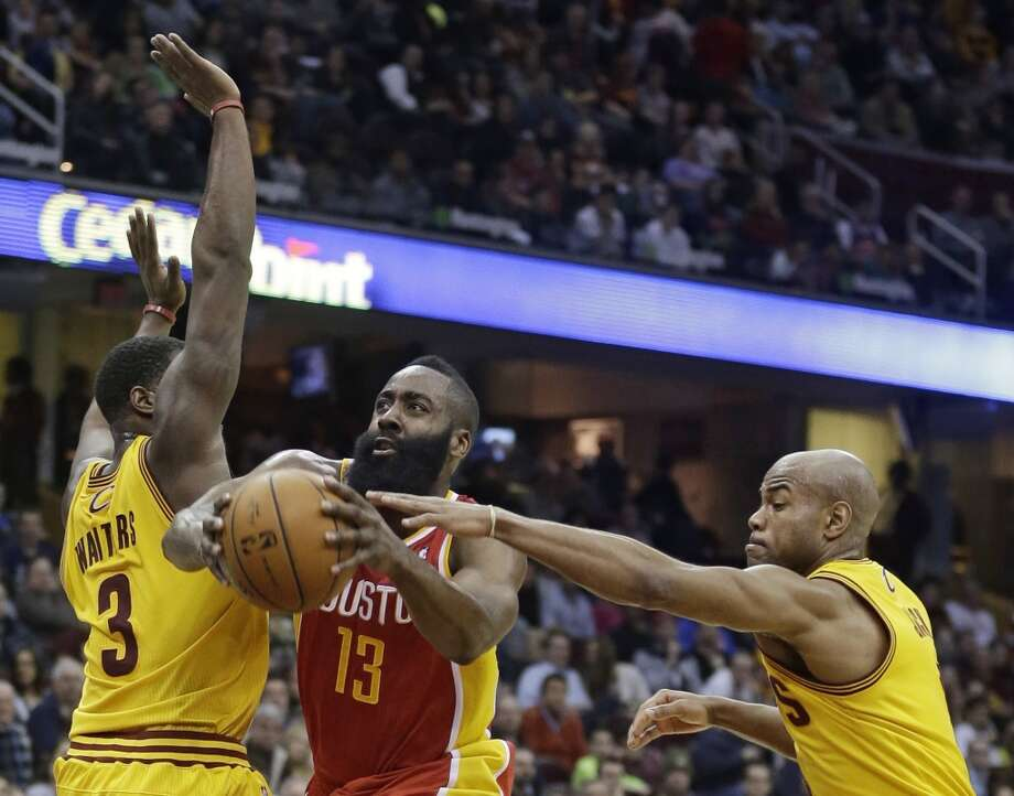 Houston Rockets' James Harden, center,  drives between Cleveland Cavaliers' Dion Waiters, left, and Cleveland Cavaliers' Jarrett Jack, right, during the third quarter of an NBA basketball game, Saturday, March 22, 2014, in Cleveland. Harden scored a team-high 37 points for Houston's 118-111 win. (AP Photo/Tony Dejak) Photo: Associated Press