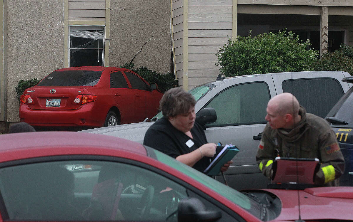 Pamela Travis (center) speaks with a San Antonio firefighter Thursday March 27, 2014 after she crashed into a building shortly before 9:00 a.m. at the Fox Fire Apartments near the intersection of Fox Trail and Blanco road. Travis said she was exiting a driveway and could not see around a parked pickup truck when she collided with a passing Ford Mustang an lost control of her vehicle. Neither driver was injured.