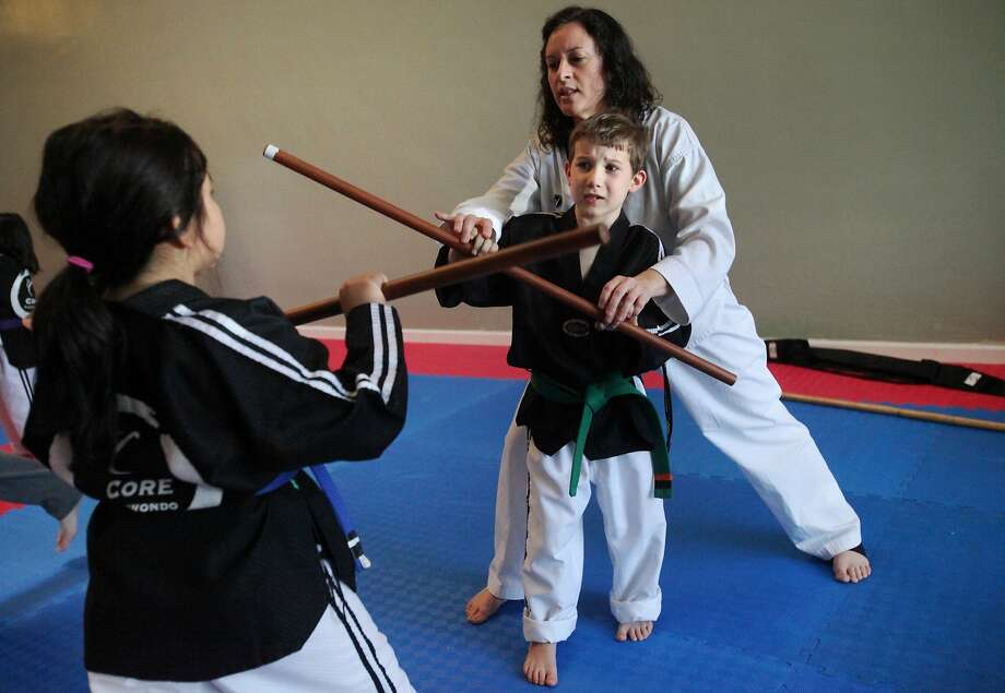 Cheryl-Lee Urbanik teaches Conrad Brousseau and Sujey Lopez how to use the long staff in a class at Core Taekwondo, which founder Meggie Felman lists on camp and after-school websites Camperoo.com and ActivityHero.com. Photo: Leah Millis, The Chronicle