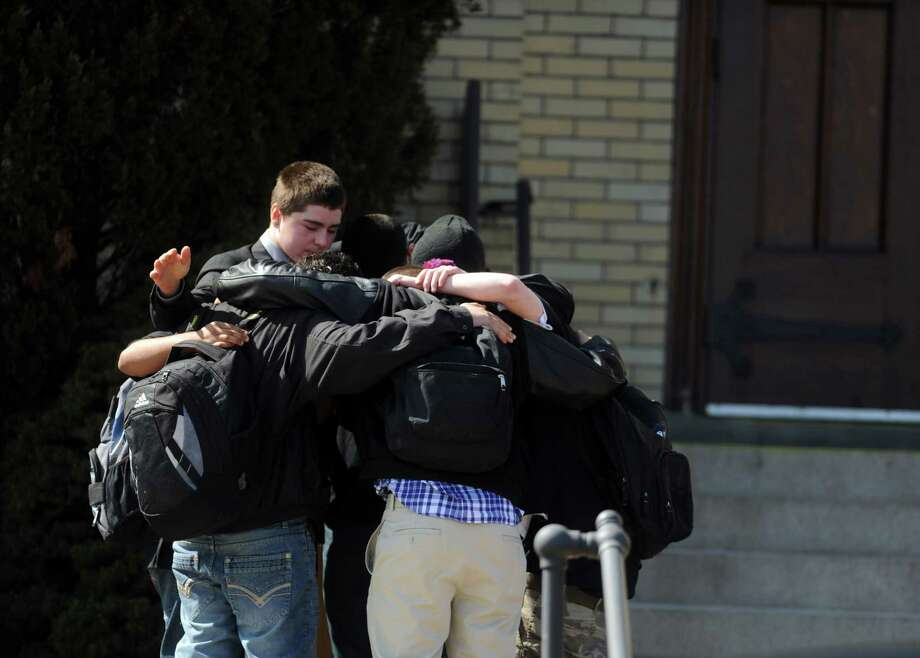 Teens embrace outside St. Joseph Church Thursday, Mar. 27, 2014, following funeral services for Kristjan Ndoj, the 15-year-old Shelton High School student who was shot on March 15 in Shelton, Conn. Photo: Autumn Driscoll / Connecticut Post