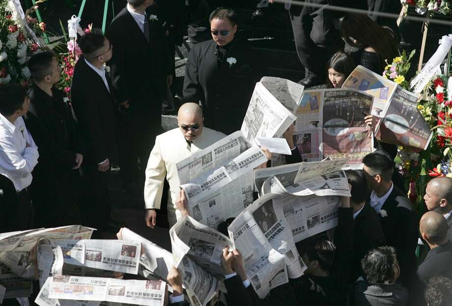 """Raymond """"Shrimp Boy"""" Chow, in a white suit, attends the funeral of slain Chinatown leader Allen Leung. Mourners are holding up newspapers to block photographers. Photo: Ming Pao Daily"""