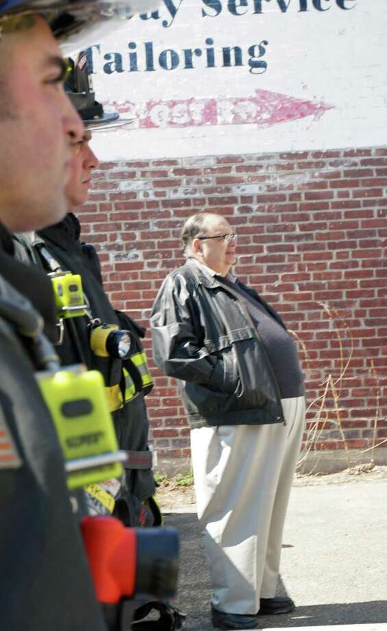 Al de Vidas, owner of Engraver's World, watches as firefighters put out a smokey fire in his store that he said started when his coffee pot malfunctioned. Photo: Genevieve Reilly / Fairfield Citizen