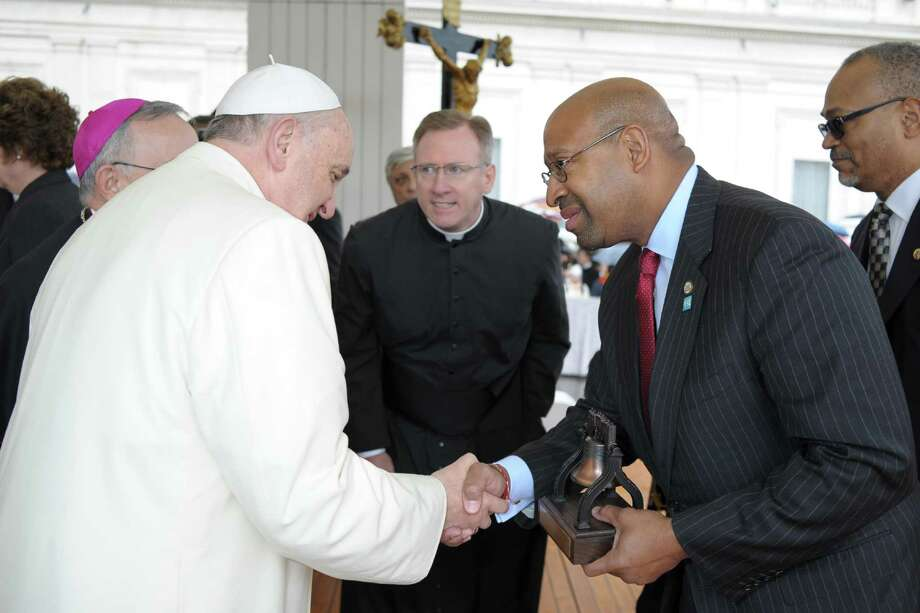 "In this picture made available by the Vatican newspaper L'Osservatore Romano, Pope Francis shakes hands with Mayor of Philadelphia Michael Nutter, at the Vatican, Wednesday, March 26, 2014. U.S. officials have made their case to the Vatican for Pope Francis to visit the U.S. next year, saying his ""message needs to be heard"" during a massive church celebration of the family planned for Philadelphia. Popes have attended five of the seven World Meetings of the Family, and Francis has made family issues the top priority of his pontificate. But no confirmation of his participation is expected before next year. (AP Photo/L'Osservatore Romano) Photo: HOPD / L'Osservatore Romano"