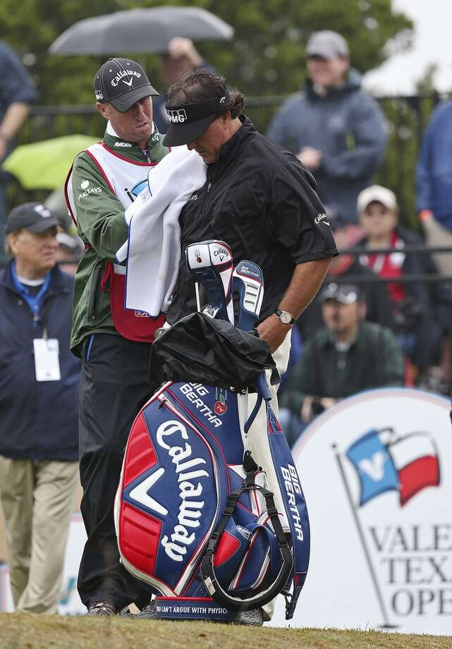 On the 10th tee, Phil Mickelson gets dried by his caddy, Jim Mackay before the start of the first round of the 2014 Texas Open at TPC San Antonio, Thursday, March 27, 2014. Photo: Jerry Lara, San Antonio Express-News