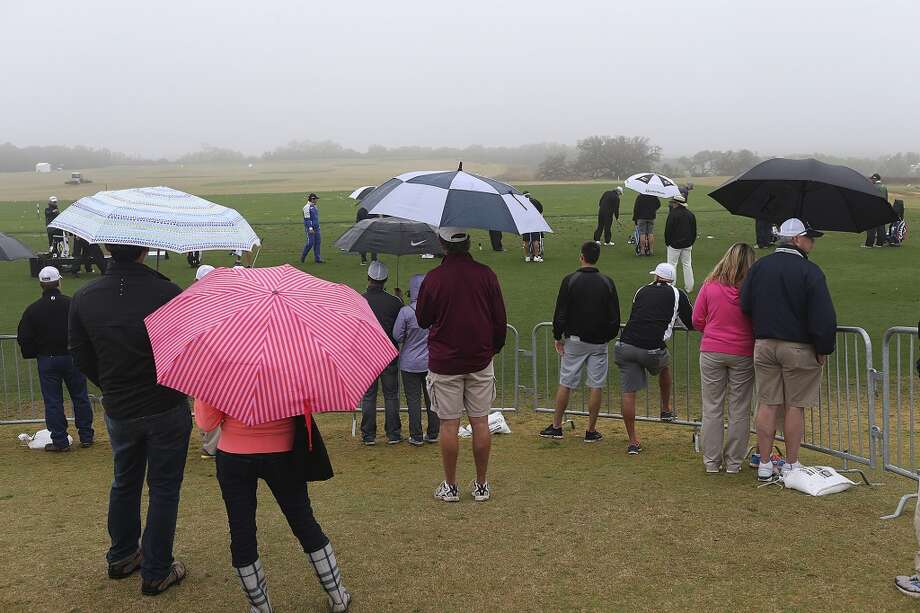 Members of the gallery watch as players warm up before the start of the first round of the 2014 Texas Open at TPC San Antonio, Thursday, March 27, 2014. The start was delayed by fog for 2 and a half hours. Photo: Jerry Lara, San Antonio Express-News