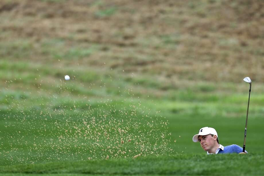 Jordan Spieth shoots out of a bunker by the 10th green during the first round of the 2014 Texas Open at TPC San Antonio, Thursday, March 27, 2014. Photo: Jerry Lara, San Antonio Express-News