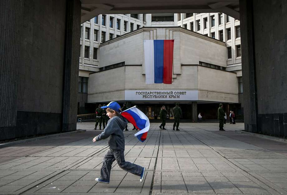 A boy runs with a Russian national flag outside the Crimean parliament in Simferopol. Photo: Alexander Polegenko, Associated Press