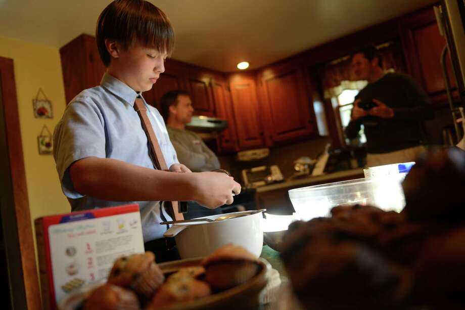 David Albright, an 8th grader at St. Mary's School, bakes muffins at his home in Milford, Conn. to deliver to the Beth El shelter in Milford. He started making muffins for the homeless when he was 8 years old. Photo: Autumn Driscoll / Connecticut Post
