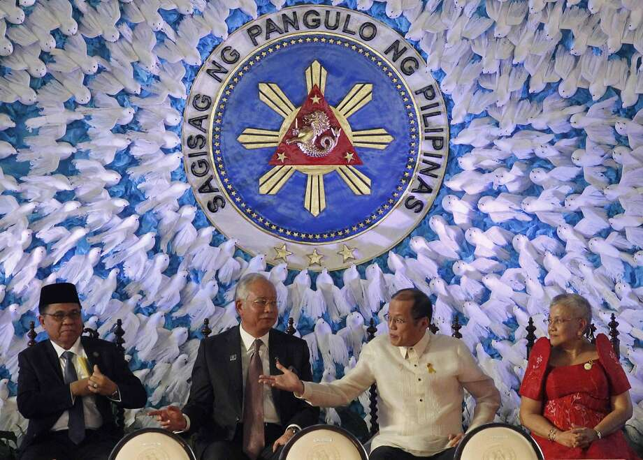 President Benigno Aquino (2nd R) gestures while talking to visiting Malaysian Prime Minister Najib  Razak (2nd L) before the signing ceremony of a final peace pact at Malacanang presidential palace in Manila March 27, 2014. The Philippines and its largest Muslim rebel group, the Moro Islamic Liberation Front (MILF), on Thursday signed a final peace pact, ending about 45 years of conflict that has killed more than 120,000 people in the country's south. ending about 45 years of conflict that has killed more than 120,000 people in the country's south. In photo from L-R:  Moro Islamic Liberation Front (MILF) Chairman Al Haj Murad Ibrahim and Presidential Adviser on the Peace Process Secretary Teresita Quintos-Deles.    REUTERS/Romeo Ranoco   (PHILIPPINES - Tags: POLITICS) Photo: Romeo Ranoco, Reuters