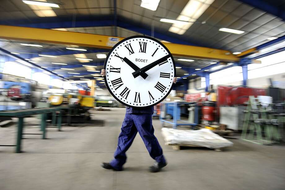 Time travel achieved: An employee of the Bodet Co. carries a clock at the plant in Trementines, 