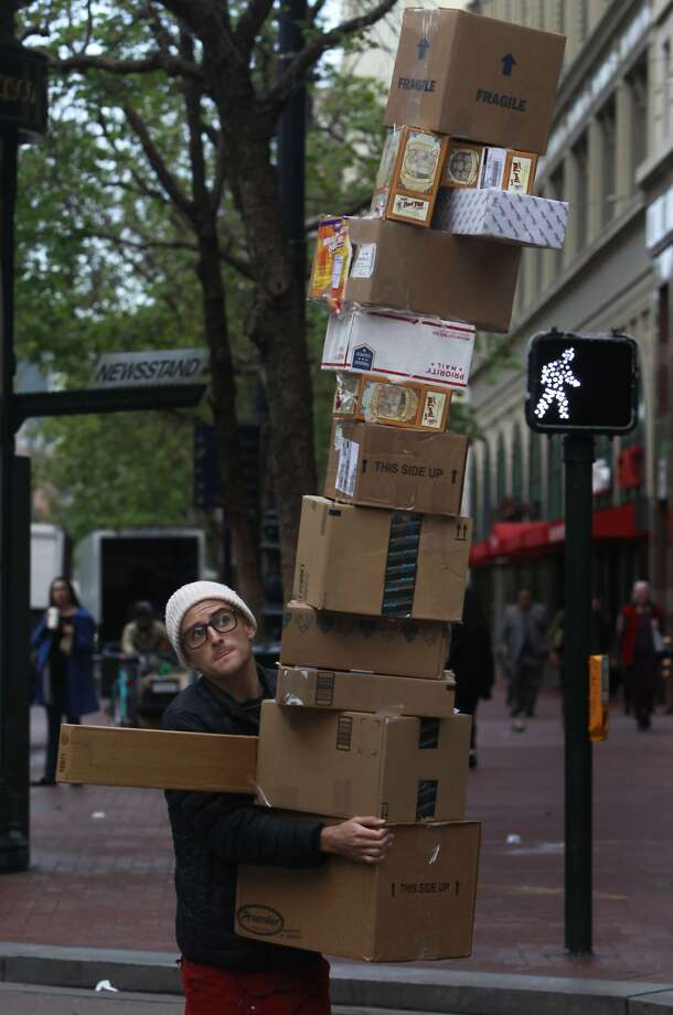 Blaine Fuller navigates the crowded sidewalk on Market Street carrying an armful of boxes in San Francisco, Calif. on Thursday, March 27, 2014. Actually, Fuller is a performance artist that creates a different idea every week that often causes passersby to do a double take. Photo: Paul Chinn, The Chronicle