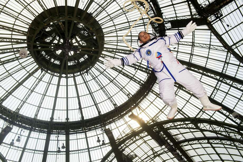 Free-floating art:Chinese performance artist Li Wei mimics an astronaut in zero gravity at the Grand Palais during the Art Paris Art Fair. Photo: Martin Bureau, AFP/Getty Images