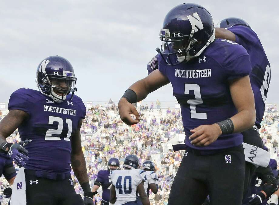 """Northwestern quarterback Kain Colter (2) wears APU for """"All Players United"""" on wrist tape and towel during a game last season. Photo: Nam Y. Huh, Associated Press"""