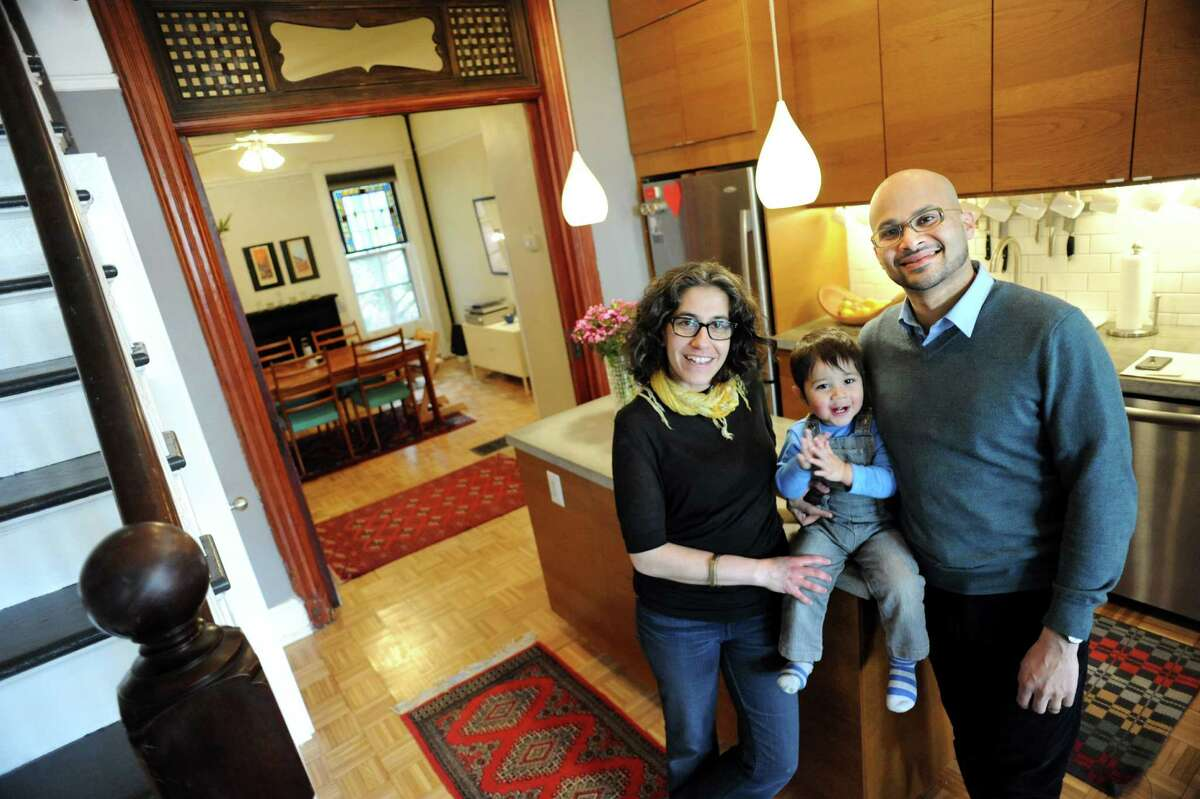 Shadi Khadivi, left, her husband Jason D'Cruz and their son Cyrus D'Cruz, 20 months, in the kitchen of their home at 56 1/2 Spring St. on Tuesday, March 25, 2014, in Albany, N.Y. (Cindy Schultz / Times Union)