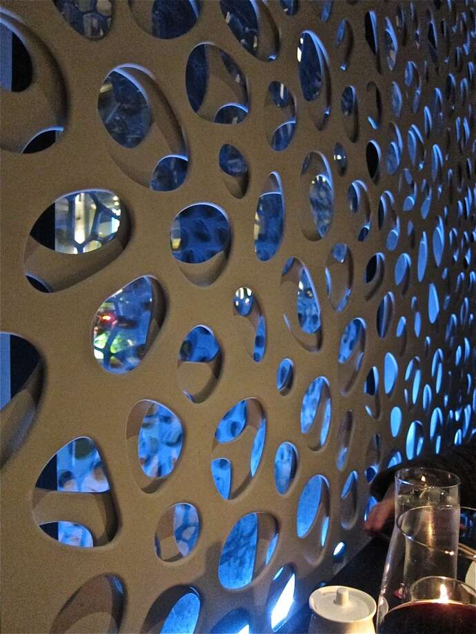 A perforated wall screen, backlit in ice blue, in the dining room at Nara.