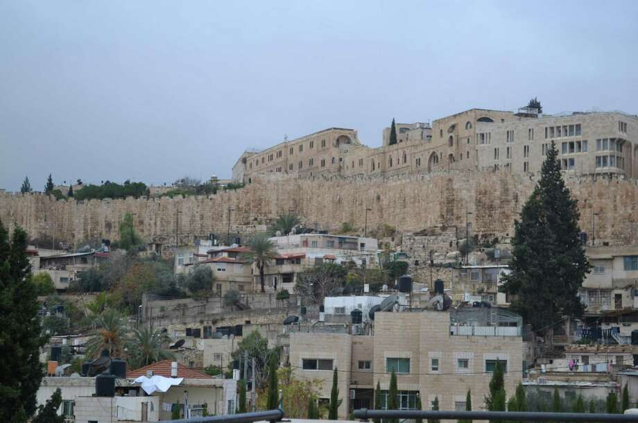 Ancient history meets the modern day in the old city of Jerusalem. Here, an ancient wall protects yesteryear boundaries while homes with modern amenities sit below. Photo: Lauren Kramer / For The Express-News