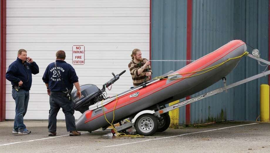 Workers wash out a boat at the fire station in Darrington as they prepare for another day of work Thursday, searching for victims of Saturday's massive mudslide in the nearby community of Oso. Photo: Ted S. Warren, Associated Press / AP2014
