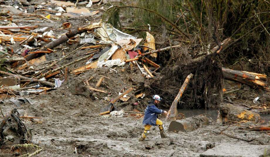 A searcher walks through mud near a massive pile of debris at the scene of a deadly mudslide Thursday in Oso. Photo: Mark Mulligan, Associated Press / Pool, The Herald