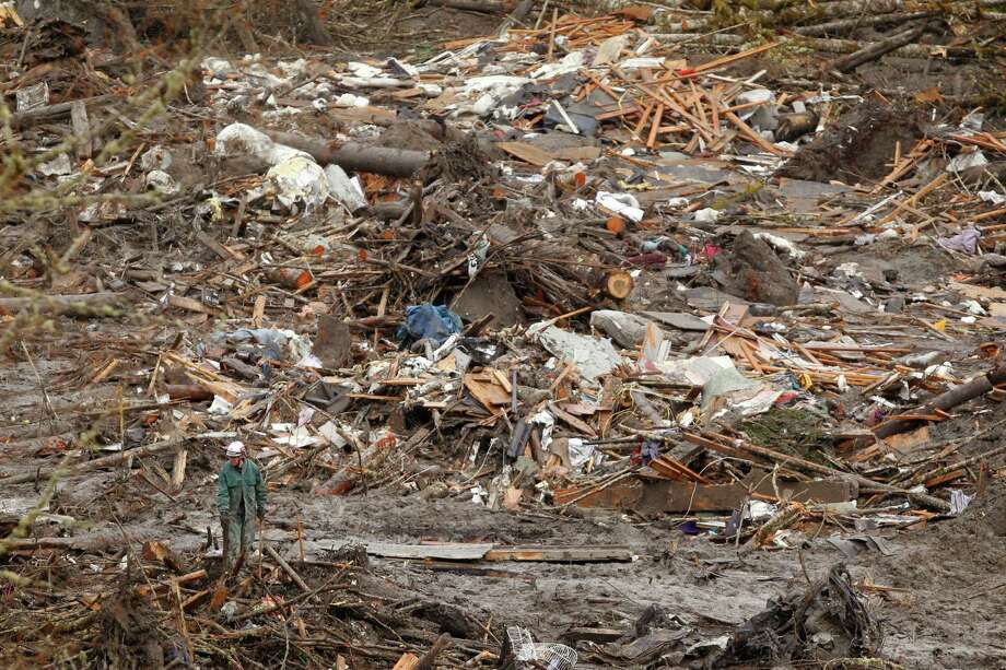 A searcher walks near a massive pile of debris at the scene of a deadly mudslide Thursday in Oso. Photo: Mark Mulligan, A / Pool, The Herald