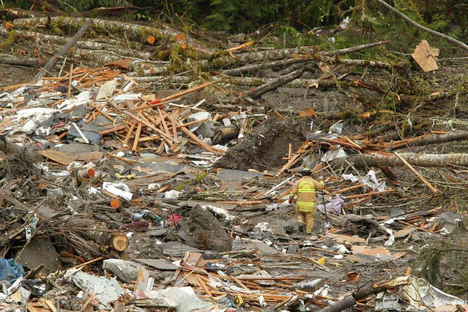 A searcher walks through a massive pile of debris at the scene of a deadly mudslide Thursday in Oso. Photo: Mark Mulligan, Associated Press / AP2014