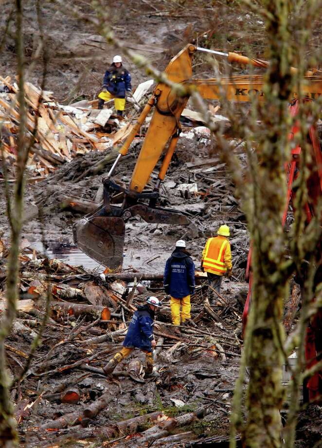 Searchers using heavy equipment work at a massive pile of debris at the scene of a deadly mudslide in Oso. Photo: Mark Mulligan, Associated Press / Pool, The Herald