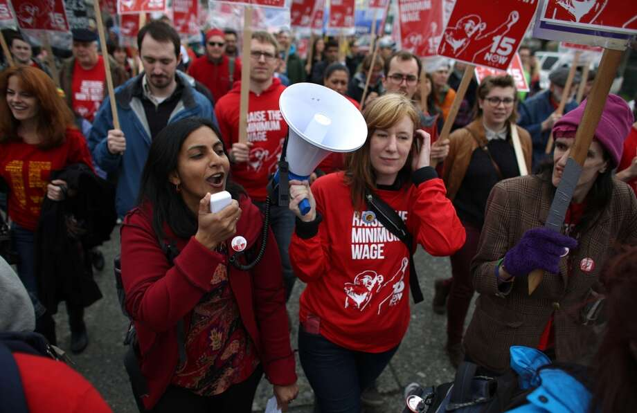 Seattle City Councilmember Kshama Sawant, left, leads a chant during a march in Seattle to raise the minimum wage to $15 per hour. Hundreds of people marched from Judkins Park to Seattle Central Community College where a rally was held. Photographed on Saturday, March, 15, 2014 in Tacoma. (Joshua Trujillo, seattlepi.com) Photo: JOSHUA TRUJILLO, SEATTLEPI.COM