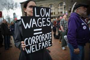 A participant holds a sign during a march in Seattle to raise the minimum wage to $15 per hour. Hundreds of people marched from Judkins Park to Seattle Central Community College where a rally was held. Photographed on Saturday, March, 15, 2014. (Joshua Trujillo, seattlepi.com)
