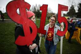 Kate Garrow and Justine Winnie hold signs during a march in Seattle to raise the minimum wage to $15 per hour. Hundreds of people marched from Judkins Park to Seattle Central Community College where a rally was held. Photographed on Saturday, March, 15, 2014. (Joshua Trujillo, seattlepi.com)