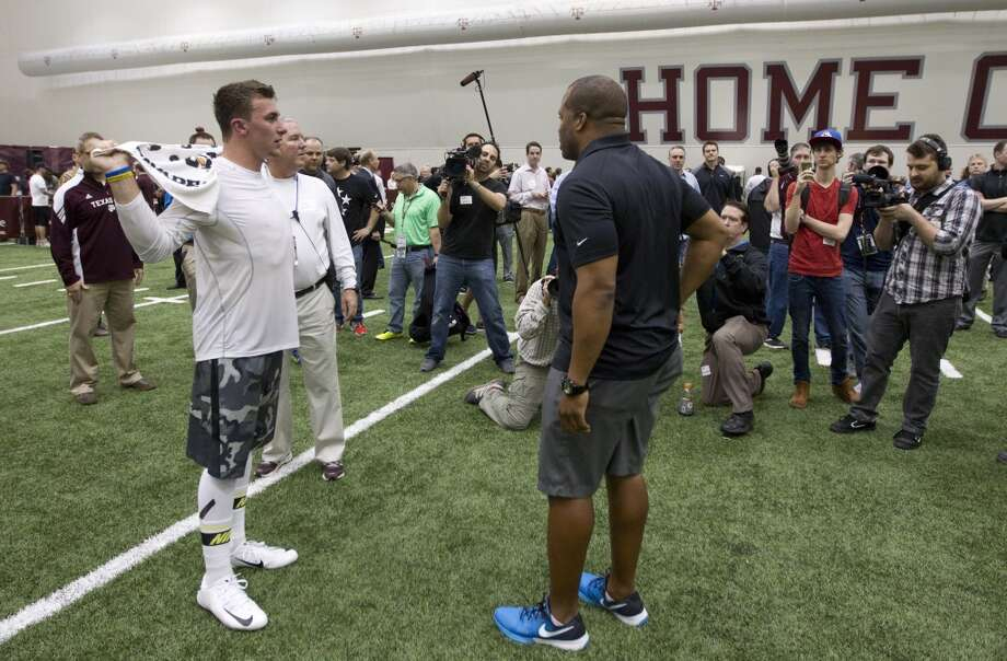 Former Texas A&M quarterback Johnny Manziel, left, talks to George Whitfield, Jr., following Manziel's pro day. Photo: Brett Coomer, Houston Chronicle