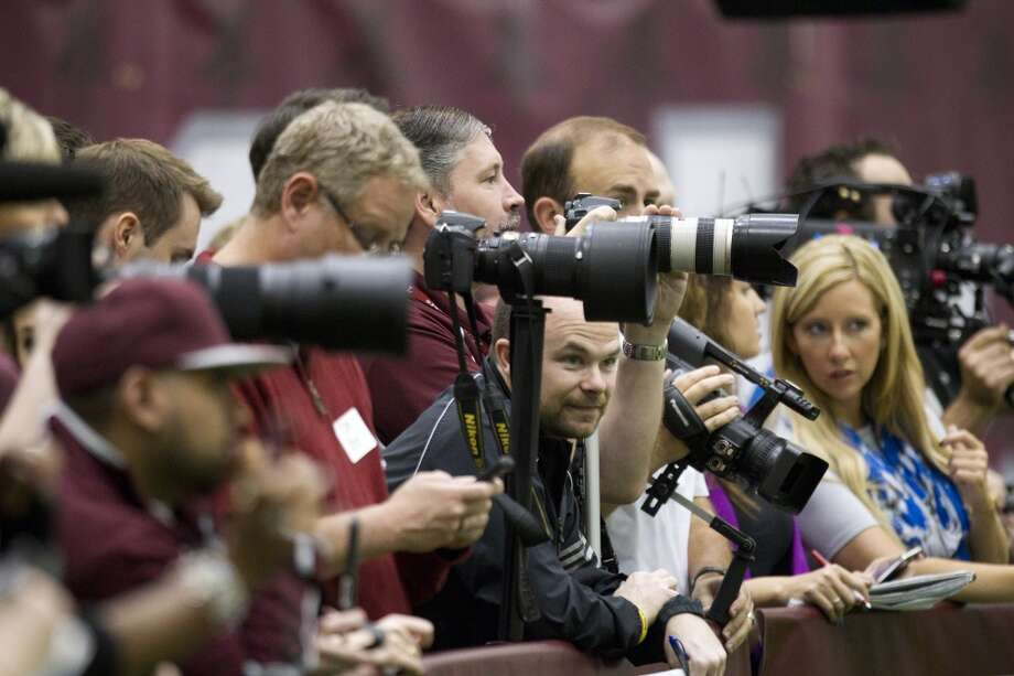Media and fans crowd against a barrier to watch Johnny Manziel's pro day. Photo: Brett Coomer, Houston Chronicle